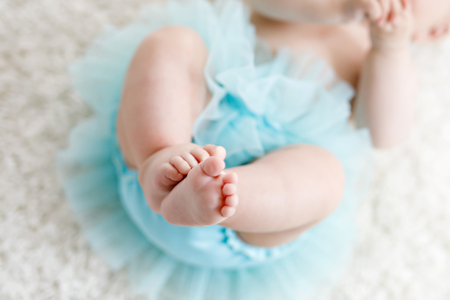Close-up of legs and feet of baby girl on white background wearing turquoise tutu skirt. Stockfoto