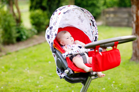 Cute little beautiful baby girl of 6 months sitting in the pram or stroller and waiting for mom