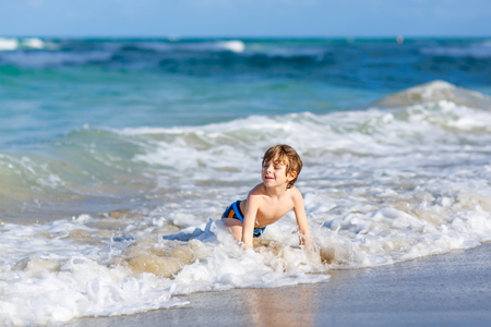 little blond kid boy having fun on ocean beach in Florida Stock Photo
