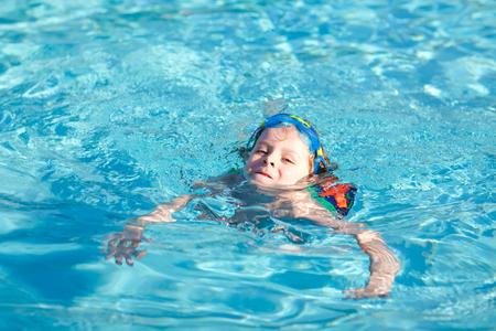 kleiner Vorschulkindjunge, der Schwimmwettbewerbssport macht. Kind mit Schwimmbrille, die den Rand des Pools erreicht. Kind, das Spaß in einem Swimmingpool hat. Aktives glückliches Kind gewinnt. Sport, aktive Freizeit. Standard-Bild