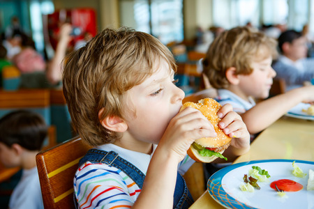 Cute healthy preschool boy eats hamburger sitting in school canteen Standard-Bild