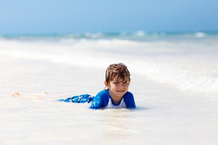 little blond kid boy having fun on tropical beach of Jamaica Stock Photo
