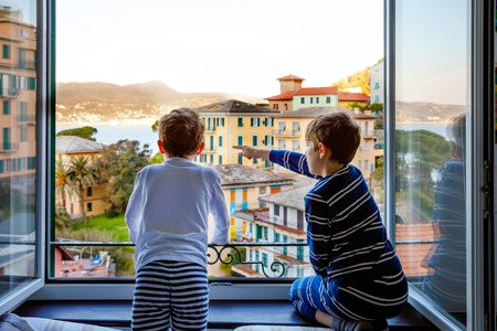 Two little kids boys enjoying view from window in morning on Liguria region in Italy. Awesome villages of Cinque Terre and Portofino. Family vacations in beautiful Italian city with colorful houses.