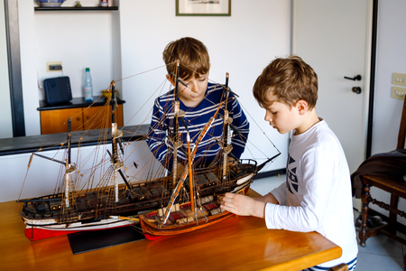 Two little kids boys playing with sailing ship model indoors. Excited children, siblings and best friends with yacht having fun after school at home. Happy twins building and creating toys Stock Photo