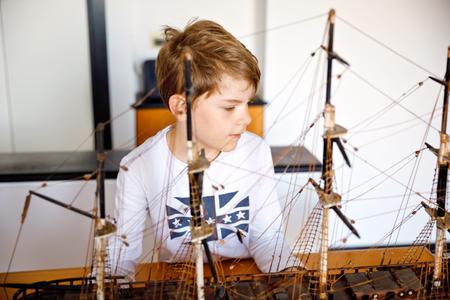 Kleine blonde school jongen jongen spelen met zeilschip model binnenshuis. Opgewonden kind met jacht plezier na school thuis. Gelukkige jongen die speelgoed bouwt en maakt