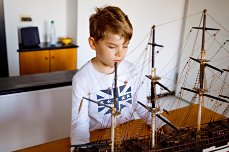 Little blond school kid boy playing with sailing ship model indoors. Excited child with yacht having fun after school at home. Happy boy building and creating toys