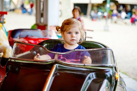 Adorable little toddler girl riding on funny car on roundabout carousel in amusement park. Happy healthy baby child having fun outdoors on sunny day. Family weekend or vacations 免版税图像