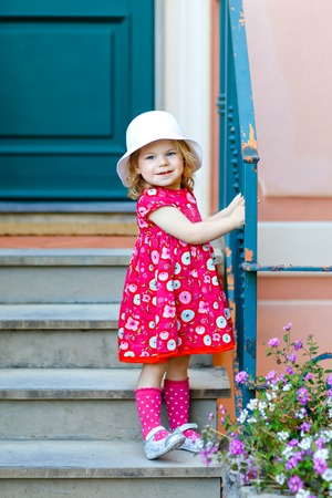 Portrait of beautiful little toddler girl in pink summer look clothes, fashion dress, knee socks and hat. Happy healthy baby child posing infront of colorful house.