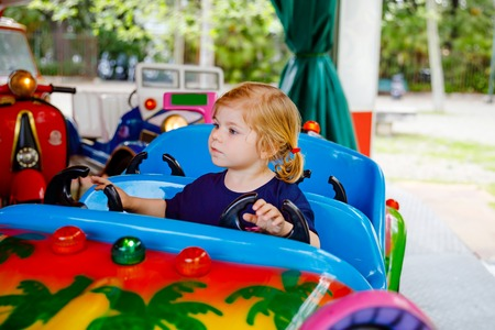 Adorable little toddler girl riding on funny car on roundabout carousel in amusement park. Happy healthy baby child having fun outdoors on sunny day. Family weekend or vacations Stock Photo