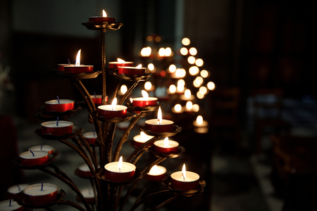 Tree like candle holder in Italian church. Warm candle light in a darch catholic church