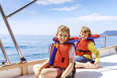 Two little kid boys, best friends enjoying sailing boat trip. Family vacations on ocean or sea on sunny day. Children smiling. Brothers, schoolchilden, siblings having fun on yacht. Banco de Imagens