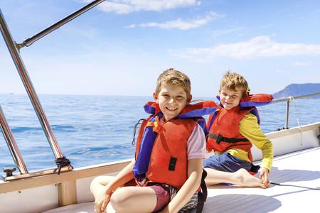 Zwei kleine Kinderjungen, beste Freunde, die eine Segelbootfahrt genießen. Familienurlaub am Meer oder Meer an einem sonnigen Tag. Kinder lächeln. Brüder, Schulkinder, Geschwister, die Spaß auf der Yacht haben. Standard-Bild