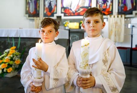 Dwóch małych chłopców do pierwszej komunii świętej. Szczęśliwe dzieci trzymając świecę do chrztu. Tradycja w kościele katolickim. Dzieci w kościele przy ołtarzu. Rodzeństwo, bracia w białych sukniach.