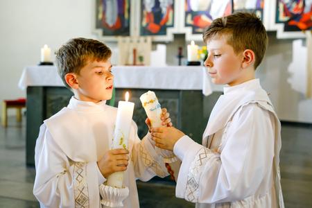 Dwóch małych chłopców do pierwszej komunii świętej. Szczęśliwe dzieci trzymając świecę do chrztu. Tradycja w kościele katolickim. Dzieci w kościele przy ołtarzu. Rodzeństwo, bracia w białych sukniach. Zdjęcie Seryjne