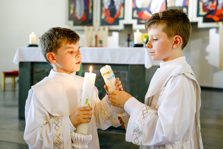 Twee kleine jongetjes die zijn eerste heilige communie ontvangen. Gelukkige kinderen die doopkaars houden. Traditie in de katholieke kerk. Kinderen in een kerk in de buurt van het altaar. Broers en zussen, broers in witte jurken. Stockfoto