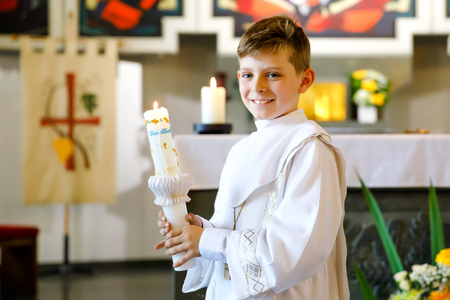 Little kid boy receiving his first holy communion. Happy child holding Christening candle. Tradition in catholic curch. Kid in a white traditional gown in a church near altar. Banco de Imagens