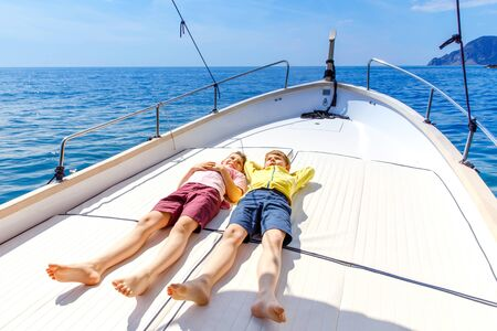 Two little kid boys, best friends enjoying sailing boat trip. Family vacations on ocean or sea on sunny day. Children smiling. Brothers, schoolchilden, siblings having fun on yacht. Stok Fotoğraf
