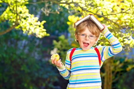 Fröhlicher kleiner Vorschuljunge mit Brille, Büchern, Apfel und Rucksack an seinem ersten Schul- oder Kindergartentag. Lustiges gesundes Kind im Freien an einem warmen sonnigen Tag, zurück zum Schulkonzept. Lachender Junge.