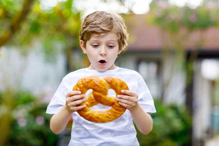 Adorable little kid boy eating huge big bavarian german pretzel. Foto de archivo