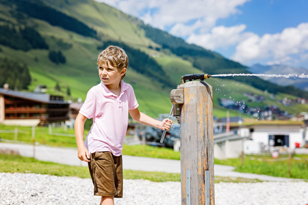 Little school kid boy playing with water pump on hot summer day