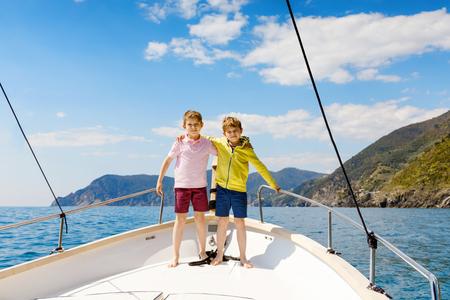 Due ragazzini, migliori amici che si godono la gita in barca a vela. Vacanze in famiglia sull'oceano o sul mare in una giornata di sole. Bambini sorridenti. Fratelli, scolari, fratelli, migliori amici che si divertono sullo yacht.