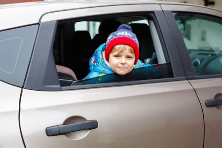 Portrait of pretty toddler boy sitting in car seat. Child transportation safety. Cute healthy kid boy looking happy about family vacations with car through window during standing in traffic jam