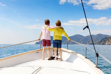 Zwei kleine Kinderjungen, beste Freunde, die eine Segelbootfahrt genießen. Familienurlaub am Meer oder Meer an einem sonnigen Tag. Kinder lächeln. Brüder, Schulkinder, Geschwister, beste Freunde, die Spaß auf der Yacht haben.