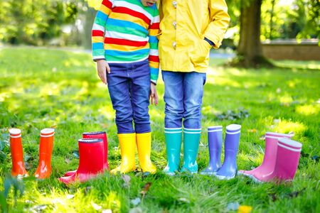 Little kids, boys and girls in colorful rain boots. Close-up of children in different rubber boots, jeans and jackets. Footwear for rainy fall