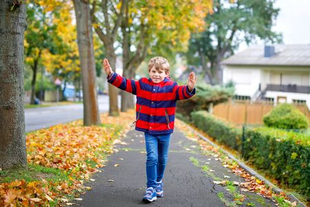 Happy little boy running on autumnal street after school. Kid happy about school vacations. Child with autumn fashion clothes walking in the city. Imagens