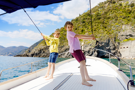Two adorable school kid boys, best friends enjoying sailing boat trip. Family vacations on sea on sunny day. Children smiling. Brothers, schoolchilden, siblings, best friends having fun on yacht.