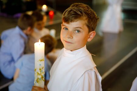 Little kid boy receiving his first holy communion. Happy child holding Christening candle. Tradition in catholic curch. Kid in a white traditional gown in a church near altar. Stok Fotoğraf
