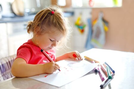 Cute little baby toddler girl painting with colorful pencils at home. Adorable healthy happy child learning drawing by usiing felt-tip pens. Active kid having fun indoors or in nursery.
