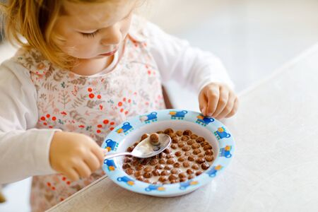 Close up of toddler girl eating healthy cereal with milk for breakfast. Cute happy baby child in colorful clothes sitting in kitchen and having fun with preparing oats, cereals. Indoors at home