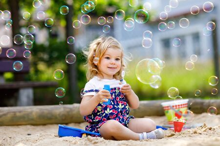 Beautiful little blonde toddler girl having fun with blowing soap bubble blower. Cute adorable baby child playing on playground on sunny summer day. Happy active funny healthy kid