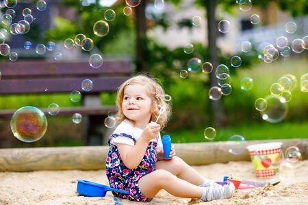 Hermosa niña pequeña rubia divirtiéndose con soplador de pompas de jabón. Niño lindo adorable bebé jugando en el patio de recreo en un día soleado de verano. Feliz niño sano divertido activo Foto de archivo