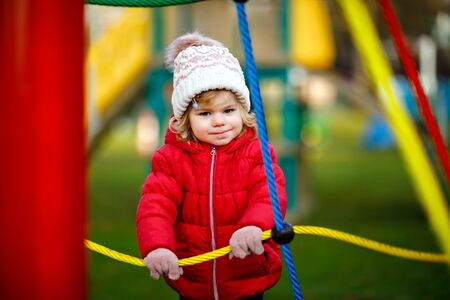 Cute toddler girl having fun on playground. Happy healthy little child climbing, swinging and sliding on different equipment. On cold day in colorful clothes. Active outdoors game for children