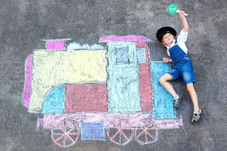 little kid boy having fun with train chalks picture