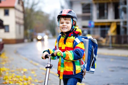 cute little school kid boy riding on scooter on way to elementary school. Child with safety helmet, school bag on rainy autumn day. Traffic in the city and schoolchildren.