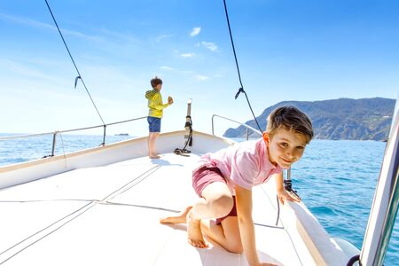 Two little kid boys, best friends enjoying sailing boat trip. Family vacations on ocean or sea on sunny day. Children smiling. Brothers, schoolchilden, siblings, best friends having fun on yacht.