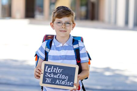 Happy little kid boy with backpack or satchel and glasses. Schoolkid on the way to school. Healthy adorable child outdoors On desk Last day third grade in German. Schools out Standard-Bild