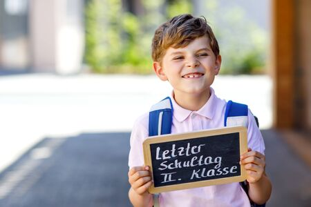 Happy little kid boy with backpack or satchel. Schoolkid on the way to school. Healthy adorable child outdoors On desk Last day second grade in German. Schools out