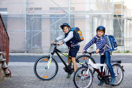 Zwei Schuljungenjungen im Schutzhelm fahren mit Fahrrad in der Stadt mit Rucksäcken. Glückliche Kinder in bunten Kleidern, die auf Fahrrädern auf dem Weg zur Schule radeln. Sicherer Weg für Kinder im Freien zur Schule Standard-Bild