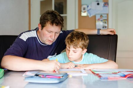Cute little school kid boy at home making homework with dad. Little child writing with colorful pencils, father helping him, indoors. Elementary school and education. 免版税图像