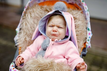 Sad crying little beautiful baby girl sitting in the pram or stroller on autumn day. Unhappy tired and exhausted child in warm clothes, fashion stylish pink baby coat with bunny ears. Stok Fotoğraf