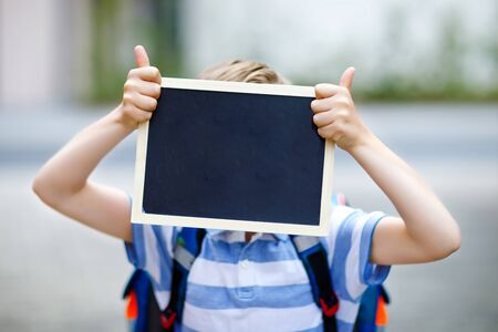 Happy little kid boy with backpack or satchel. Schoolkid on the way to school. Healthy adorable child outdoors With chalk desk for copyspace. Back to school or schools out. Unrecognizable face