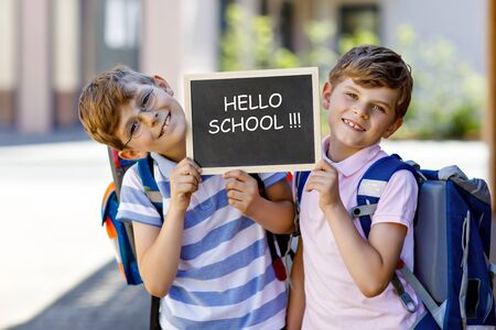 Two little kid boys with backpack or satchel. Schoolkids on the way to school. Healthy children, brothers and best friends outdoors on street. Hello school on chalk desk. Happy siblings 免版税图像