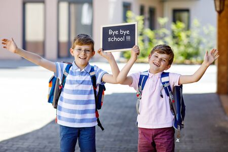Two little kid boys with backpack or satchel. Schoolkids on the way to school. Healthy children, brothers and best friends outdoors on street. Bye bye school on chalk desk. Happy siblings. Standard-Bild - 127447172