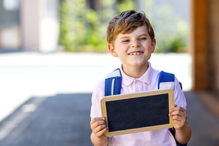 Happy little kid boy with backpack or satchel and glasses. Schoolkid on the way to school. Healthy adorable child outdoors. Empty chalk desk for copy space in hands. Schools out or back to school