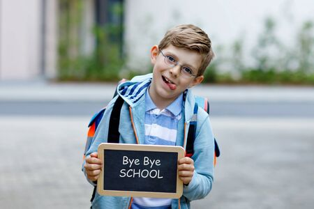 Happy little kid boy with backpack or satchel and glasses. Schoolkid on the way to school. Healthy adorable child outdoors On chalk desk Bye bye school. Back to school concept