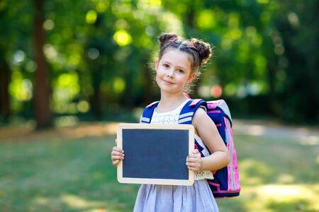 Glückliches kleines Mädchen, das mit Schreibtisch und Rucksack oder Schulranzen steht. Schulkind am ersten Tag der Grundschule. Gesundes entzückendes Kind draußen, im grünen Park. Copyspace leerer Schreibtisch